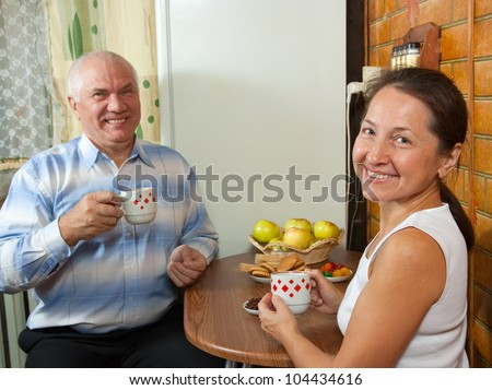 Mature couple at breakfast time at kitchen interior