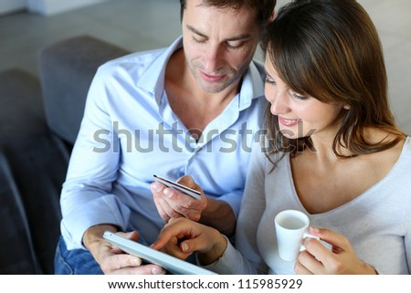 Mature couple at home using credit card to shop online