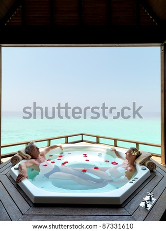 stock photo : Mature couple bathing in jacuzzi of spa center - Copyspace