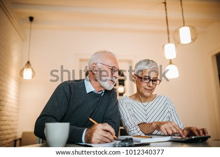 Mature couple doing some paperwork and calculations at home
