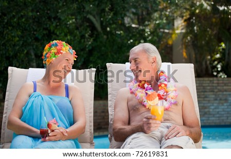 Mature couple drinking a cocktail  beside the swimming pool at home