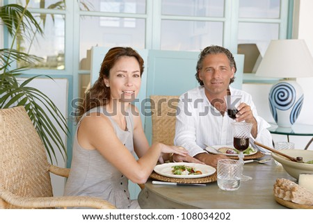 Mature couple eating and drinking together at garden table, smiling at the camera.