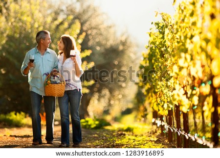 Mature couple enjoy romantic walk through vineyard while tasting wine. #1283916895