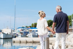 Mature couple enjoying a day at the coast walking away from the camera hand in hand past a small boat harbour