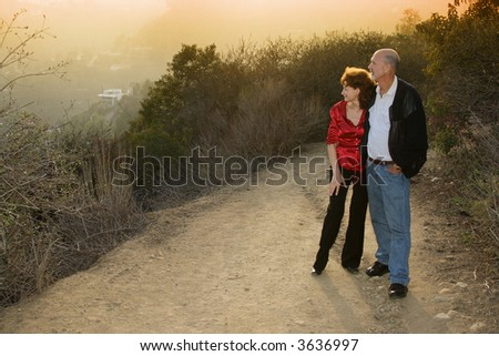 Mature couple enjoying sunset on a trail outdoors.