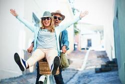 Mature couple enjoying while riding bicycle on street