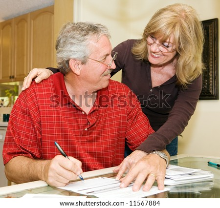 Mature couple happy about paying off their debts.