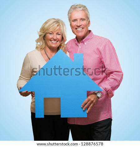 Mature Couple Holding Model Of A House against a blue background