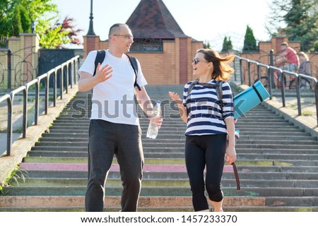 Mature couple in city on stairs, middle-aged man and woman in sportswear talking walking. Active sports healthy lifestyle of age people