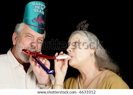Mature couple in New Years party hats blowing noise-makers.  Isolated on black.