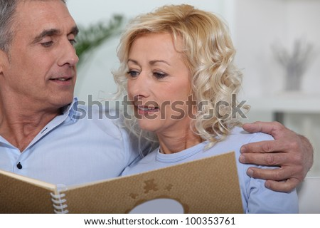 stock photo : Mature couple looking at a photo album. Save to a lightbox ▼