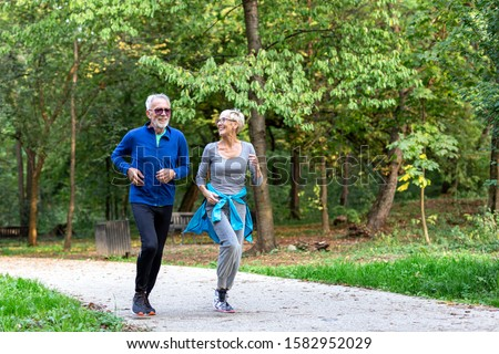 Mature couple man and woman jogging in the park