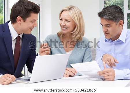 Mature Couple Meeting With Financial Advisor At Home - Shutterstock ID 550421866