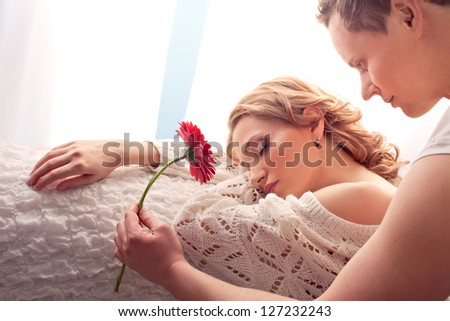 Mature couple of lovers. Man presents flower sleeping woman