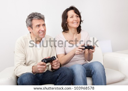 Mature couple playing videogames at home in the couch