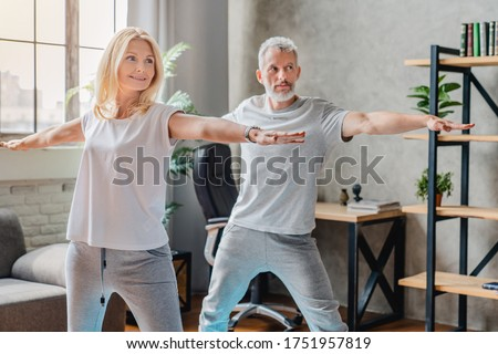 Mature couple practicing yoga and performing warrior yoga pose together
