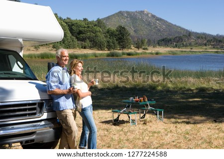 Mature couple relaxing in countryside by lake on motor home vacation