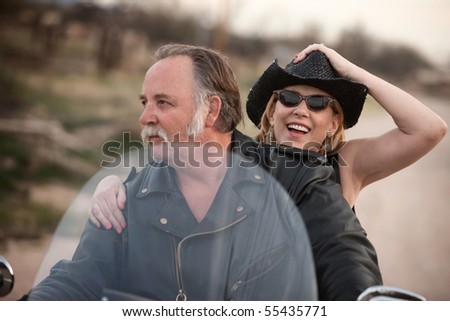 Mature couple riding on a motorcycle in the desert