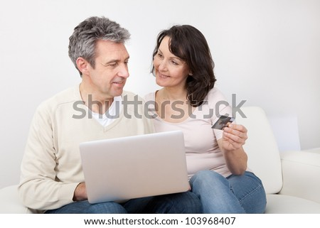 Mature couple shopping in internet using laptop at home
