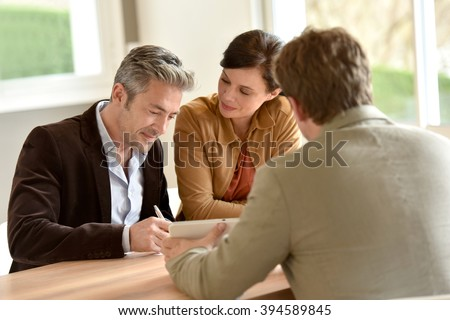 Mature couple signing documents in real-estate agency