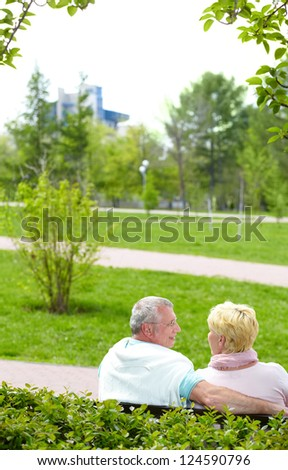 Mature couple sitting and talking in park in summer - stock photo