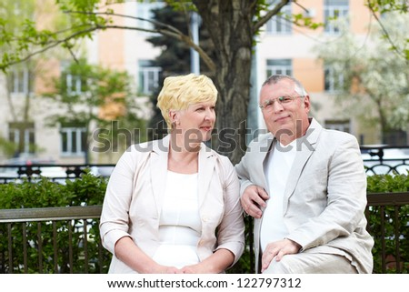 Mature couple sitting on bench in park in summer
