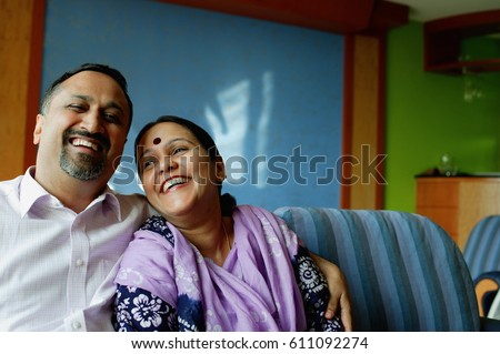 Mature couple sitting side by side, smiling