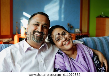 Mature couple sitting side by side, smiling at camera, portrait