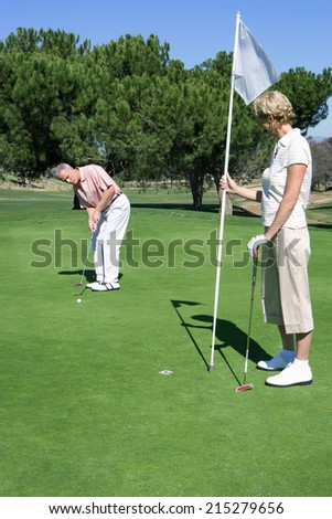 Mature couple standing on putting green, man playing shot, woman holding golf flag, watching