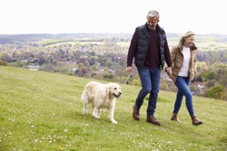 Mature Couple Taking Golden Retriever For Walk