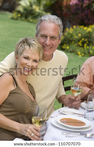 Mature couple toasting wine together