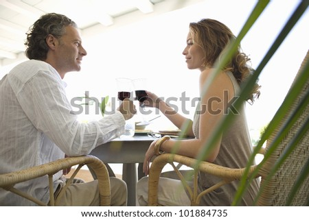 Mature couple toasting with red wine while having lunch in a hotel.