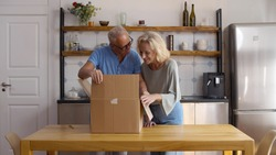 Mature couple unpack cardboard box or parcel in kitchen. Happy retired man and woman receiving food delivery and open box with groceries together