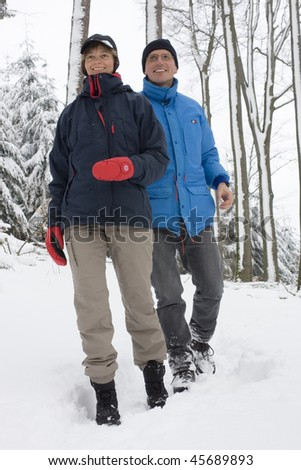 Mature couple walking in the snow in winter