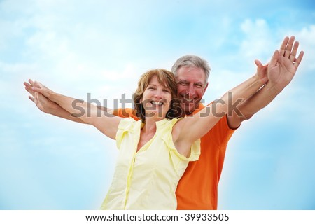 Mature couple with arms outstretched over a blue sky background stock photo