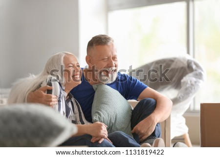 Mature couple with belongings indoors. Moving into new house #1131819422