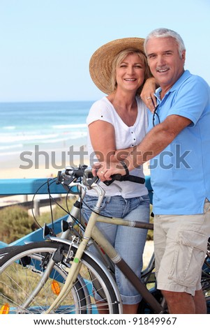 Mature couple with bikes by a beach