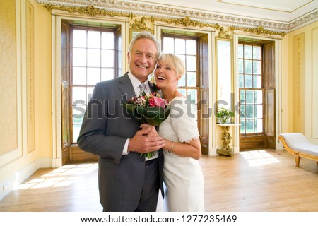 Mature couple with bouquet celebrating on wedding day at camera
