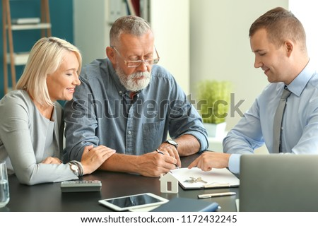 Mature couple with estate agent in office