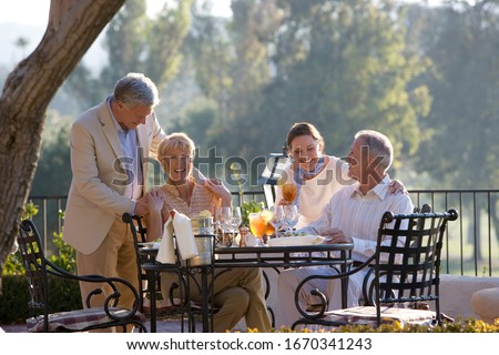 Mature couple with friends dining at outdoor restaurant table