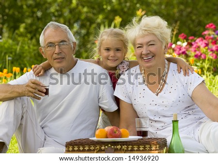 Mature couple with grandchild picnicked on the grass