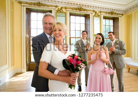 Mature couple with guests celebrating on wedding day at camera