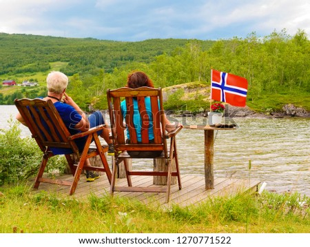 Mature couple woman and man relaxing outdoor, sitting on wooden chairs on lake fjord shore. Holidays relaxation and trip. Norway Scandinavia Europe. #1270771522