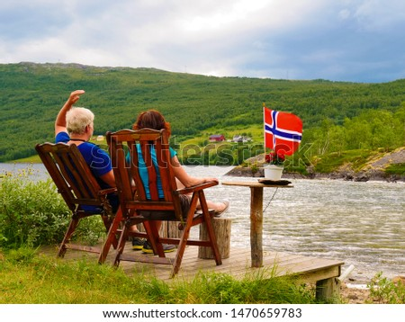 Mature couple woman and man relaxing outdoor, sitting on wooden chairs on lake fjord shore. Holidays relaxation and trip. Norway Scandinavia Europe.