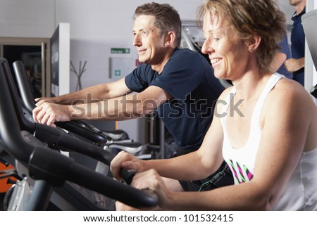 Mature couple working out at fitness center