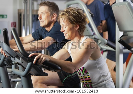 Mature couple working out at fitness center on exercise bikes