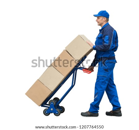 Mature Delivery Man Carrying Cardboard Boxes On Hand Truck Over White Background
