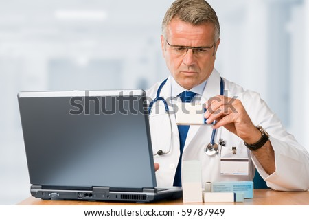 Mature doctor examining a medication's case to make prescriptions in his clinic office *Please note: the Doctor Label is made by myself with a personal design*