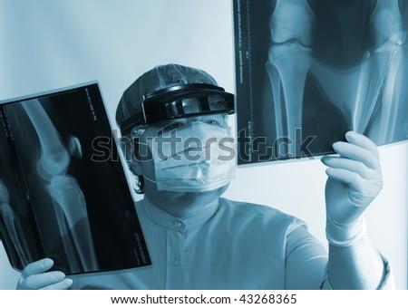 Mature doctor examining X-ray image near window #43268365