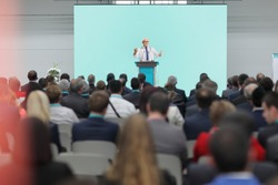 Mature doctor giving a speech on a stage at a conference in front of an audience